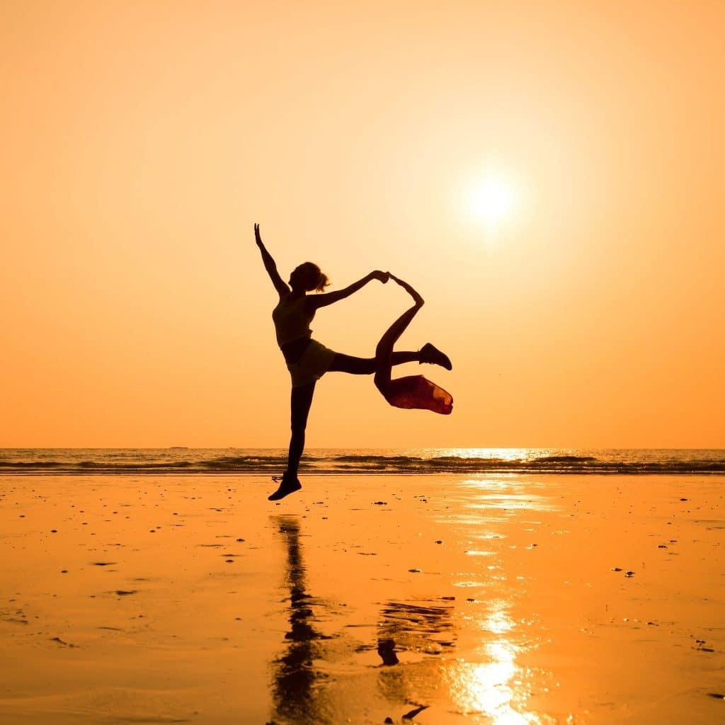 Silhueta de uma mulher pulando na praia.