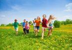 Grupo de crianças com quatro meninos e três meninas correndo em gramado durante o dia.
