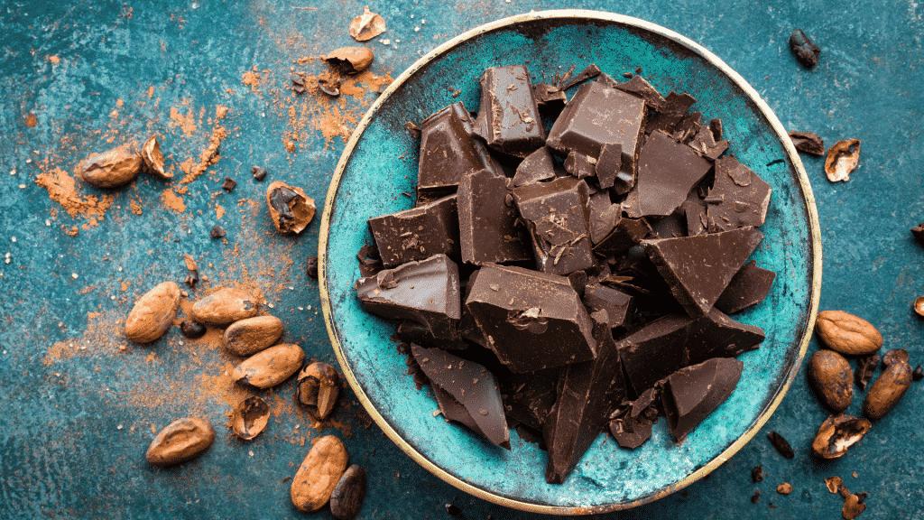 Pedaços de chocolate amargo em uma tigela com amêndoas do lado