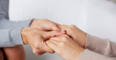 Pessoa segurando mãos de outra pessoa