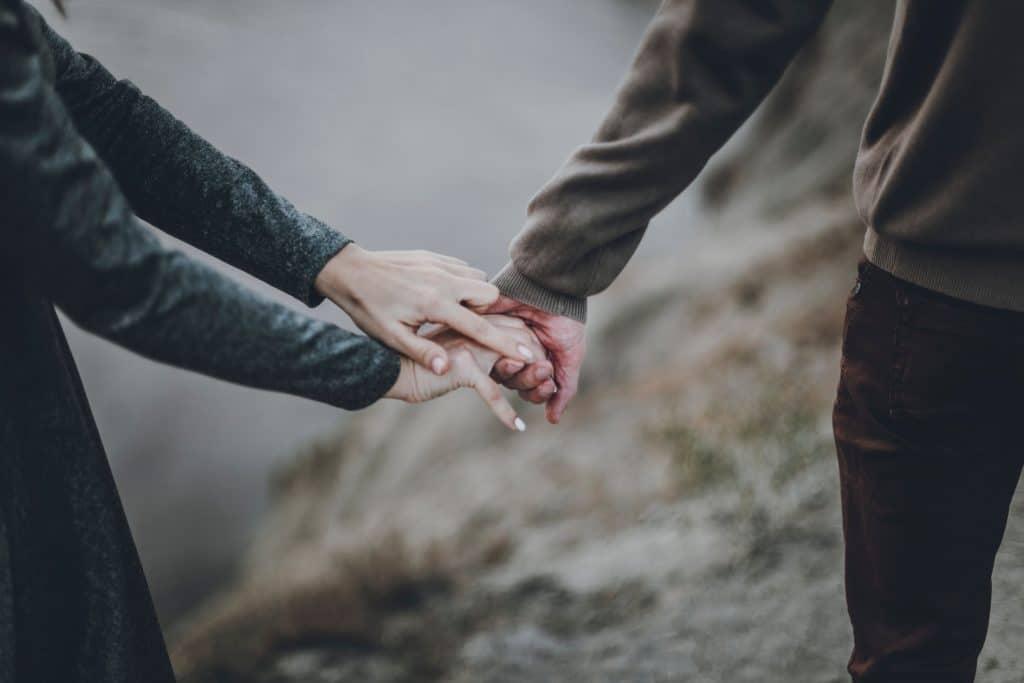 Mulher segurando mãos de um homem