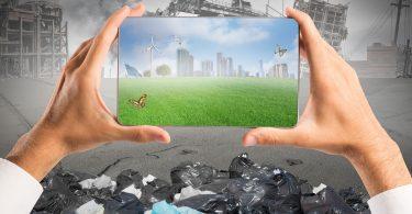 Lugar destruído com prédios caídos, lixo no chão e fumaça. Duas mãos seguram um tablet no centro da imagem, que mostra uma cidade com grama verde, paines de energia solares, captadores de energia eólica e prédios bonitos.