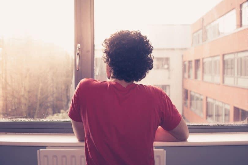Homem de cabelos cacheados de costas, reflexivo, olhando pela janela.