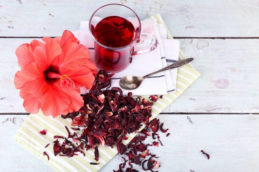 Chá de hibisco servido em uma caneca de vidro. Está sobre uma mesa de madeira pintada na cor brnaca. Ao lado da caneca, uma flor de hibisco e flores secas para o chá.