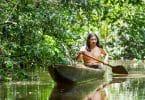 Homem indígena andando de canoa em rio.