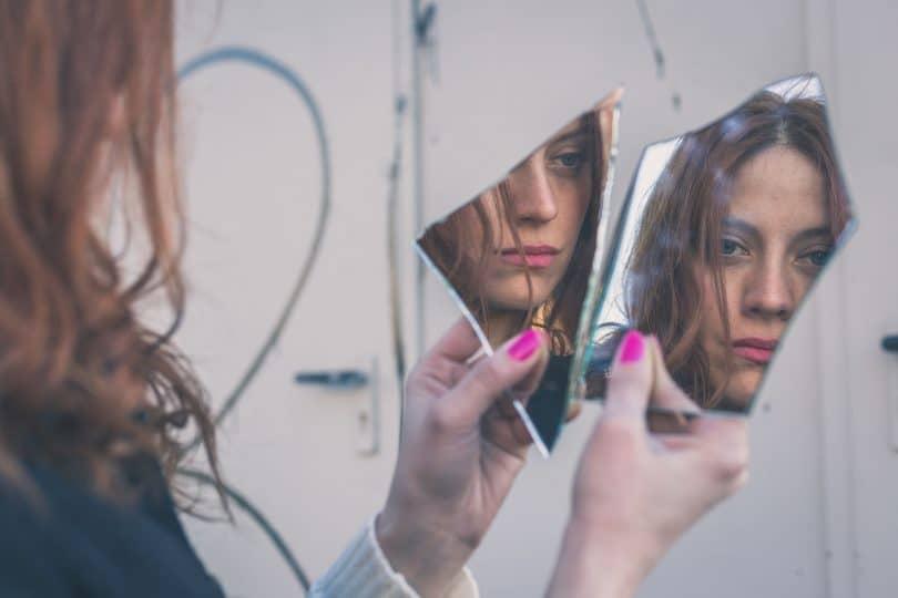 Mulher olhando seu reflexo no espelho triste