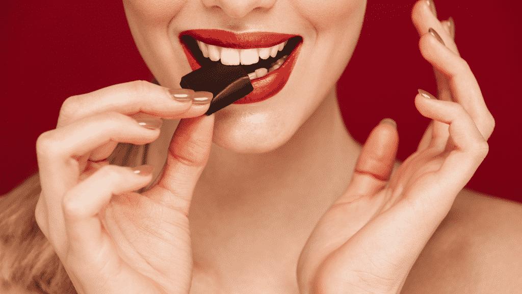 Mulher comendo pedaço de chocolate