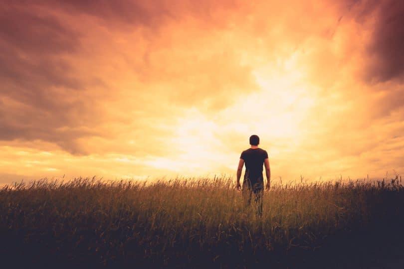 Silhueta de um homem em pé, de costas, em um campo sob o pôr do sol.