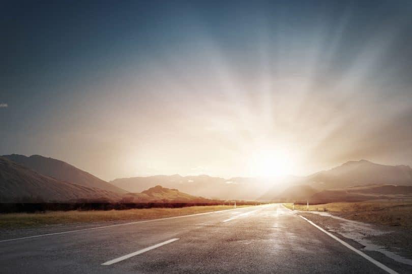 Sol nascendo no caminho da estrada
