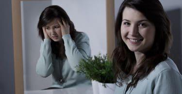 Mulher sorrindo enquanto seu reflexo no espelho está triste