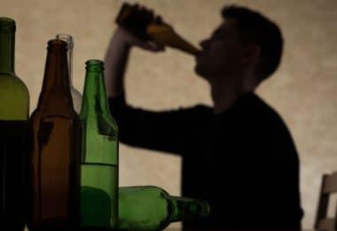 Sombra de jovem bebendo com garrafas de bebida vazias em foco