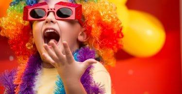 Criança com peruca colorida, óculos de festa e enfeites ao redor do pescoço. Sua boca está aberta e sua mão esquerda também, com a palma virada para cima.