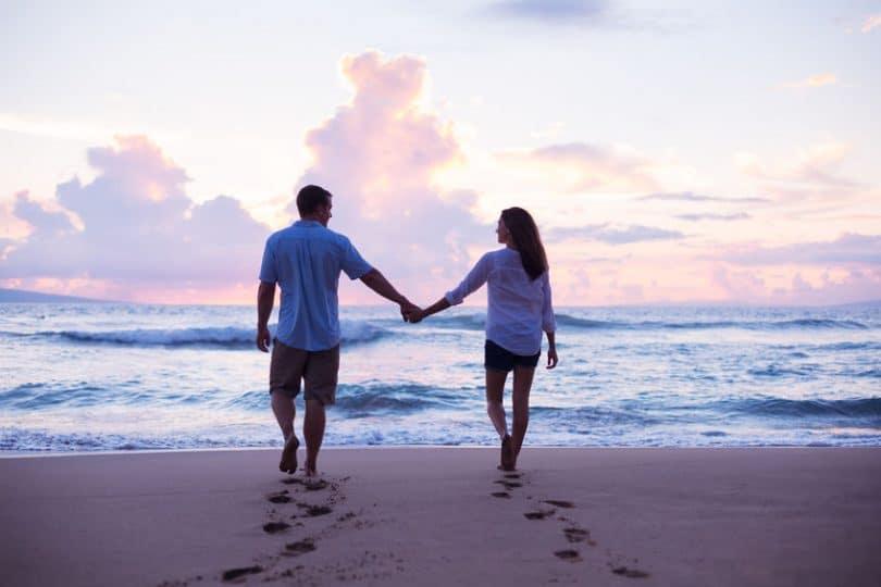 Casal de costas caminhando na praia