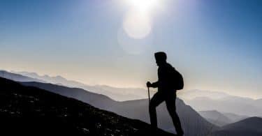 Silhueta de pessoa caminhando em direção ao topo de uma montanha, usando capuz e mochila.