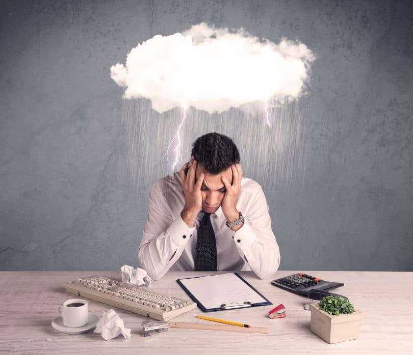 Homem com o rosto apoiado nas mãos, em cima de uma mesa. Em frente, uma prancheta, um teclado de computador, uma calculadora, uma xícara com café, uma caixa, papeis amassados e materiais de escritório. Em cima do homem, o desenho de uma nuvem com raios e chuva.