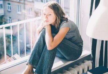 Adolescente sentada ao lado da janela apoiando sua cabeça no joelho pensativa