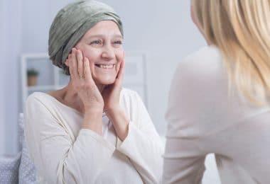 Mulher com câncer olhando e sorrindo para outra mulher a sua frente