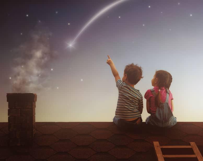 Menino e menina sentados no telhado de casa de costas olhando para estrela cadente