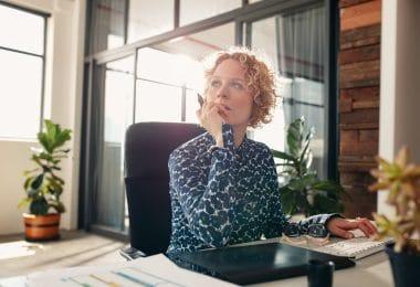 Mulher olha para o lado com semblante reflexivo enquanto está sentada em um escritório, trabalhando.