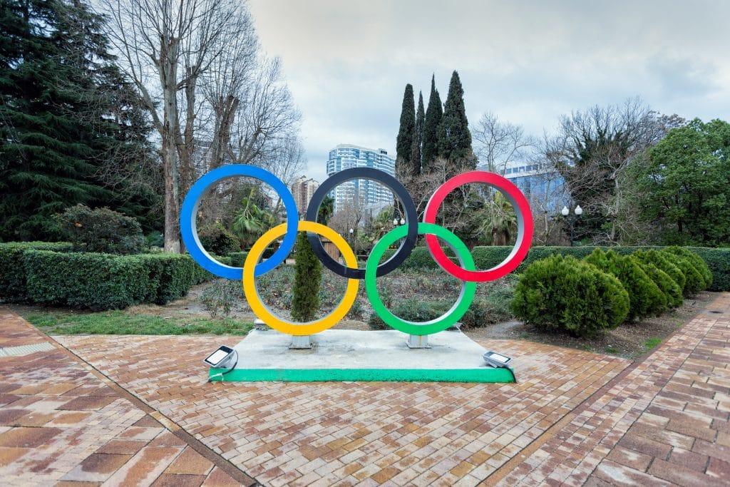 Imagem dos anéis do símbolo das Olímpiadas feito em formato de uma estátua. Ele está disponível em um lindo jardim.