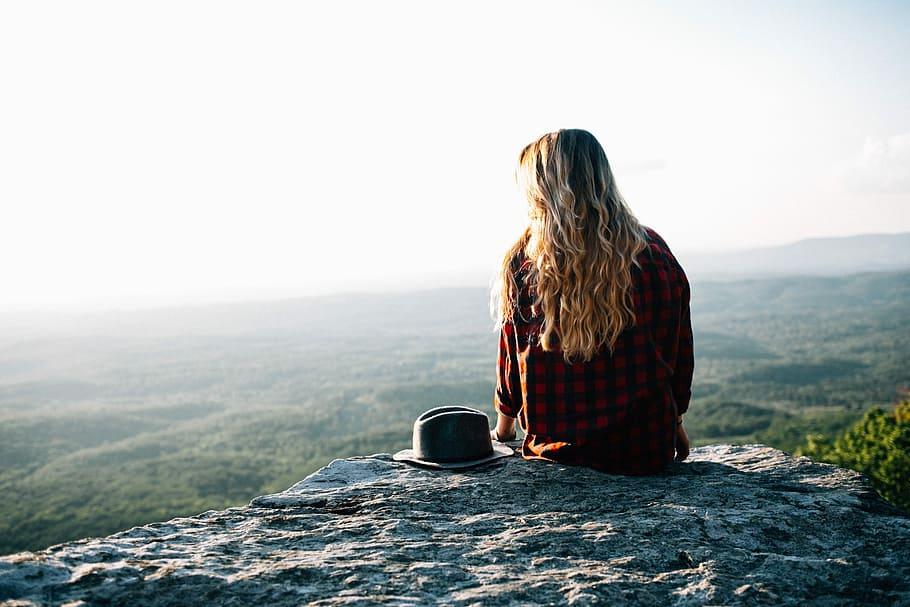 Mulher sentada no topo de uma montanha, com um chapéu ao seu lado.