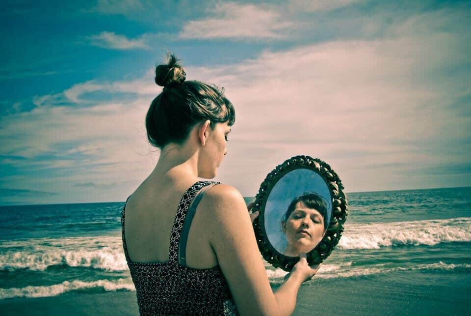 Mulher na praia segurando um espelho com seu reflexo