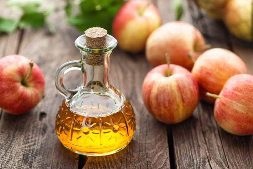 Vinagre de maçã em frasco. Sobre a mesa também há maçãs.