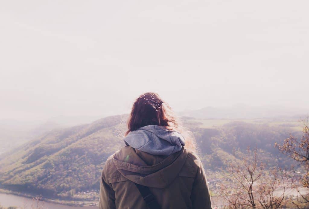 Mulher olhando para as montanhas a sua frente