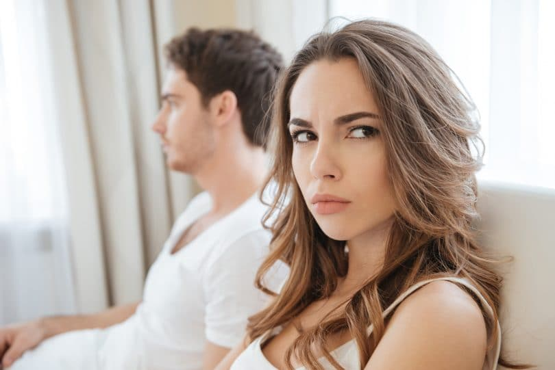 Mulher com cara de desconfiada ao lado de seu namorado.