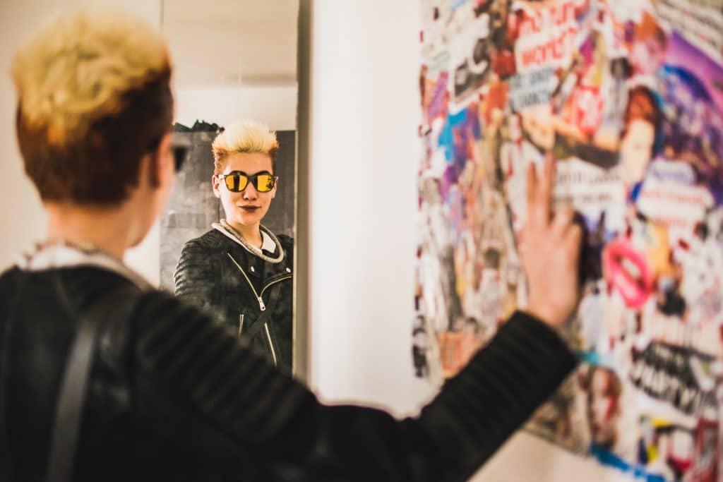 Mulher olhando para o espelho apoiando na parede