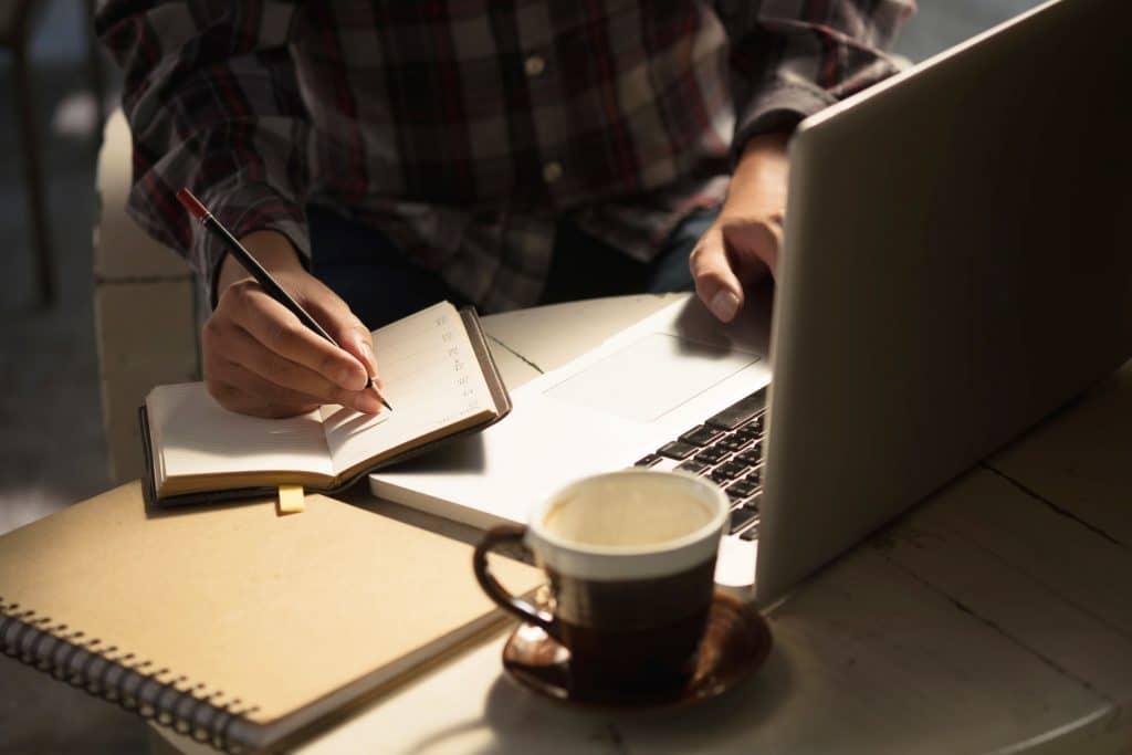 Homem escrevendo e mexendo no notebook.