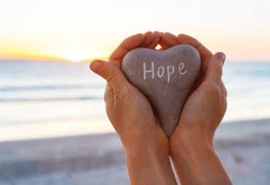 """Mãos unidas segurando pedra escrito """"Hope"""" com praia ao fundo"""