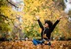 Mulher sentada com os braços abertos no gramado com folhas caídas.