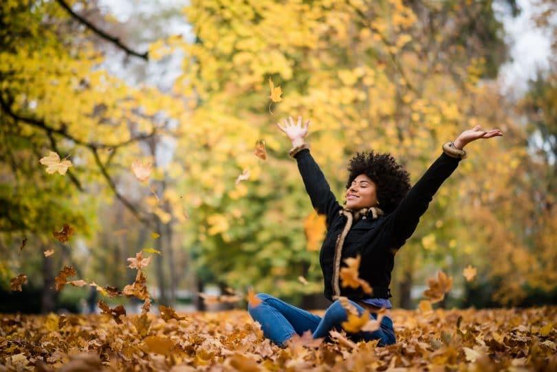 Mulher sentada com os braços abertos no gramado com folhas caídas