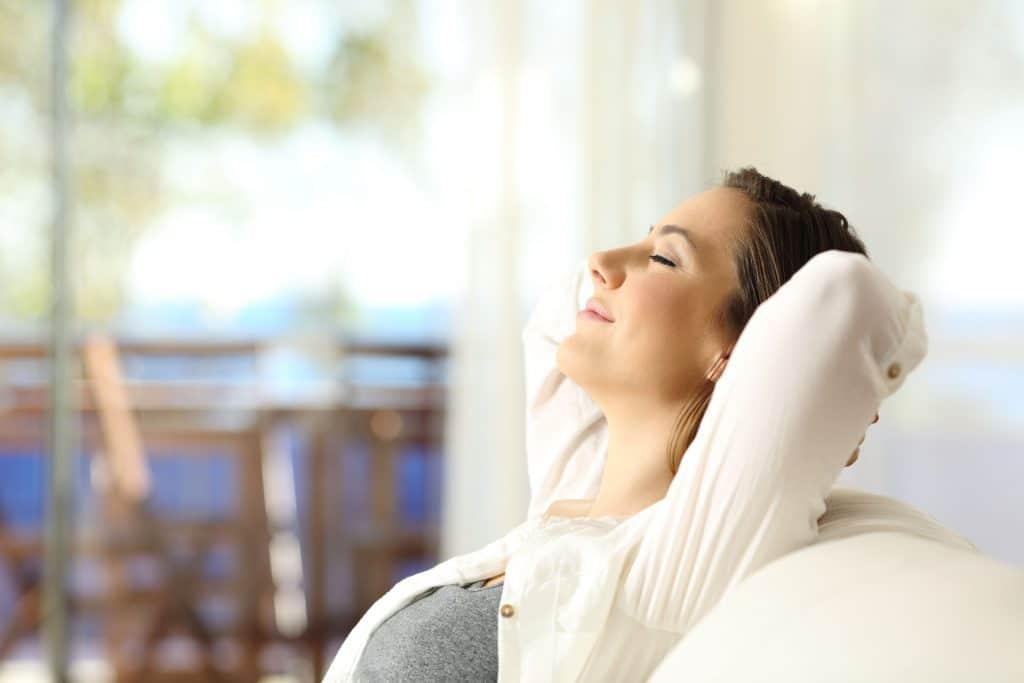 Mulher sentada em sofá com os olhos fechados, descansando sua cabeça com as mãos para trás, a segurando.