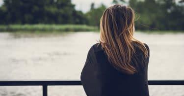 Mulher de costas, apoiada em uma barreira de metal, olhando para um rio na sua frente.