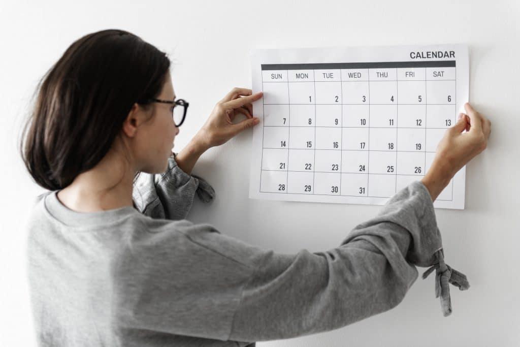 Mulher colocando calendário na parede.