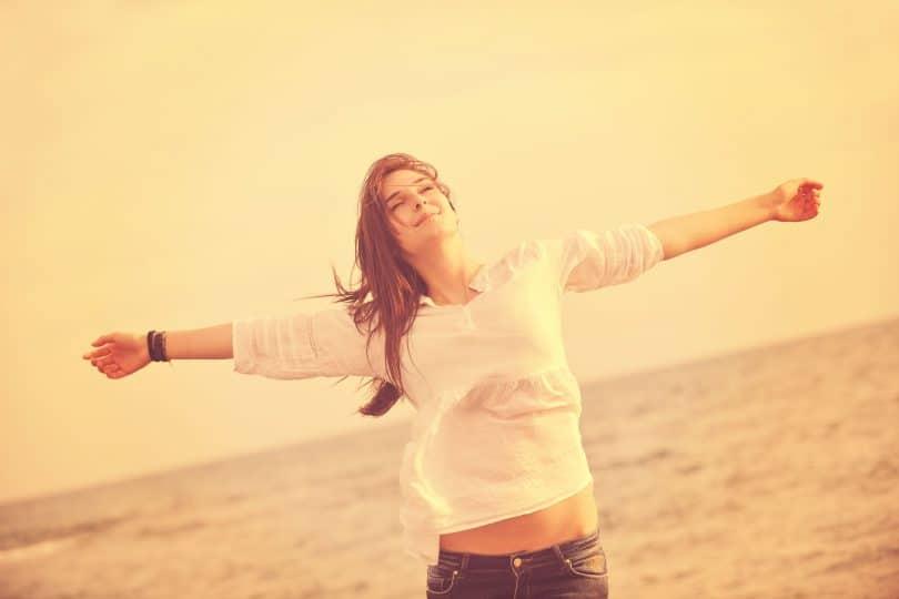 Mulher de braços abertos e olhos fechados em uma praia, sentindo o vento em sua direção.
