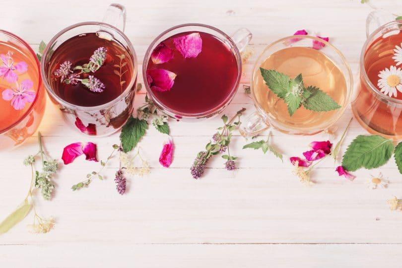 Xícaras com diferentes tipos de chás e plantas sobre uma mesa de madeira.