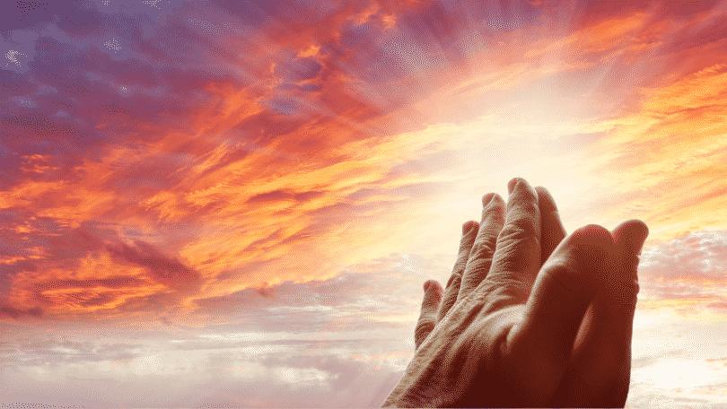 Mãos levantadas para o céu, em sinal de oração