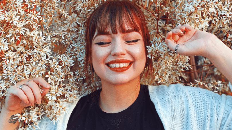 Mulher de olhos fechados e sorrindo, encostada em um arbusto florido