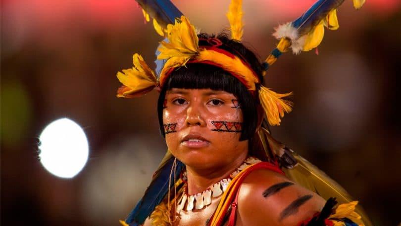 Mulher olhando para frente com traços de tinta no rosto e na cabeça uma tiara com penas ao redor