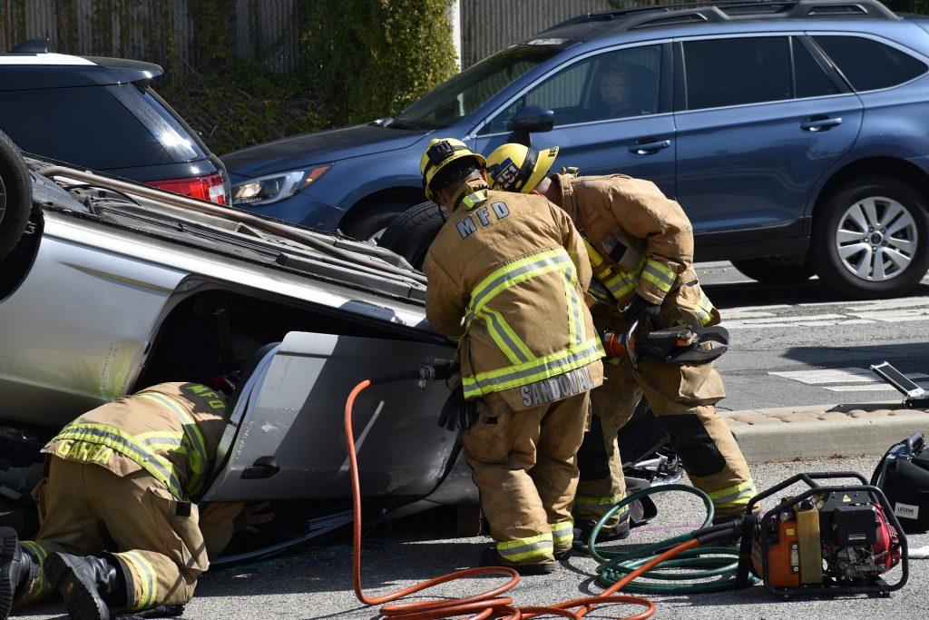 Imagem de um acidente de capotamento de carro. O acidente foi grave e as vítimas estão sendo socorridas por três homens do resgate.