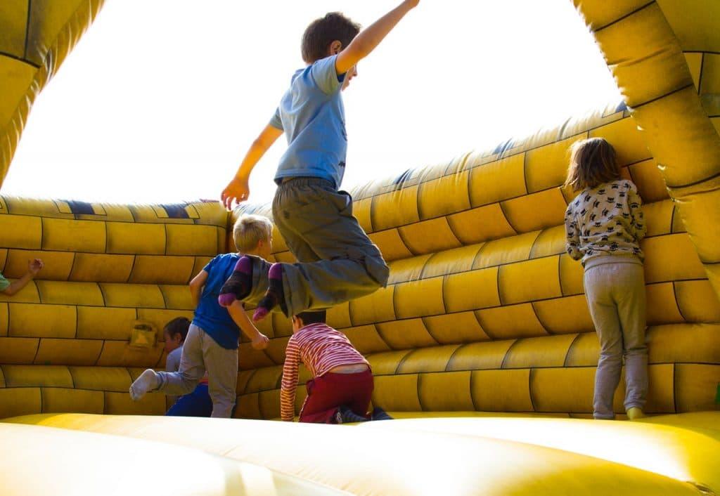 Crianças pulando em pula-pula inflável, com paredes amarelas.