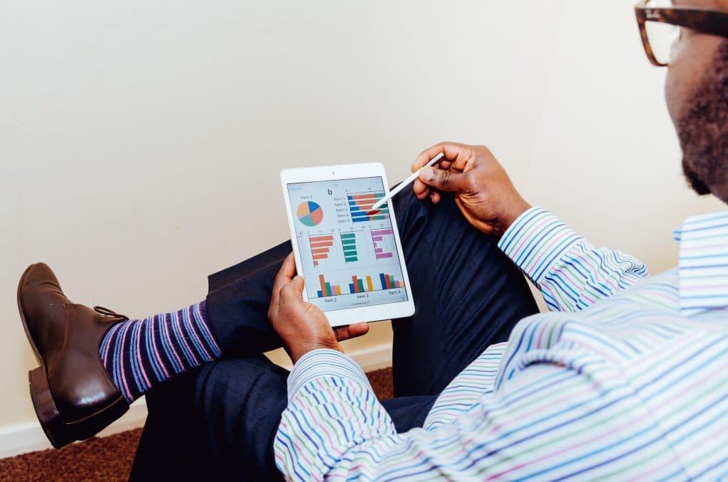 Homem sentado com iPad na mão analisando gráficos
