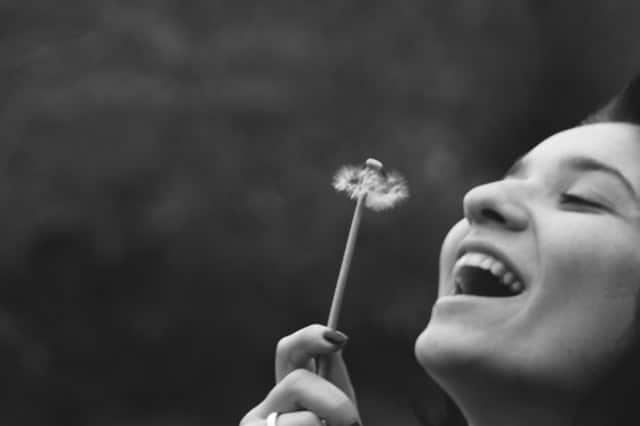 Meio rosto de mulher sorrindo com flor dente-de-leão na mão em preto e branco