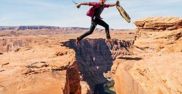 Homem pulando vão que está no chão.