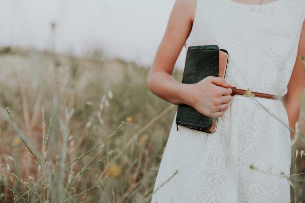 Mulher de vestido caminhando em um campo de flores, durante o dia, segurando uma Bíblia junto ao corpo.