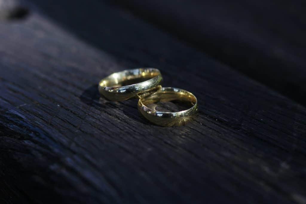 Imagem de um par de alianças de ouro disposta sobre uma madeira escura.