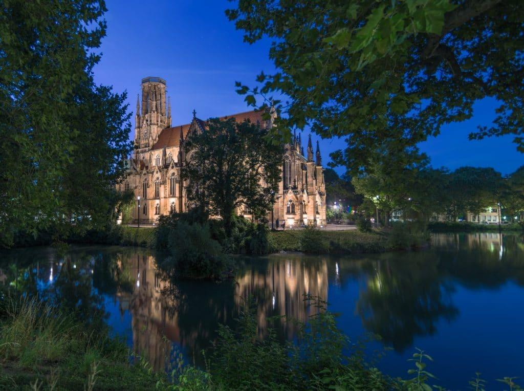 Castelo antigo, cercado por árvores e um lago, durante a noite.